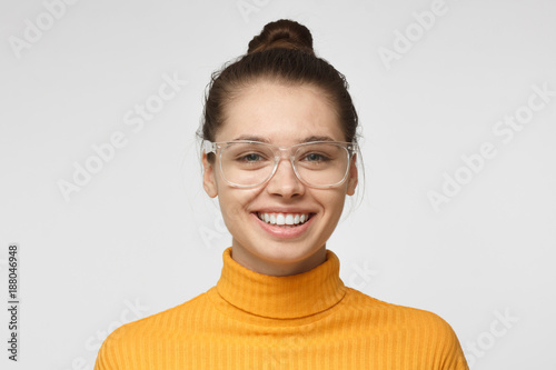 Fotografiet  Close up shot of smiling and laughing attractive young woman in yellow polo neck