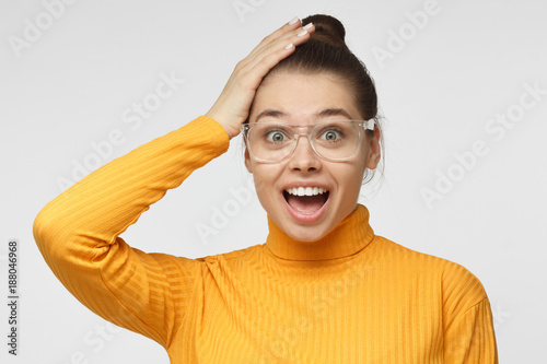 Obraz na plátne Casual dressed young female in yellow sweater shouting oh my god with open mouth