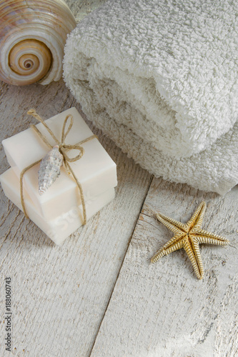 Fotografie, Obraz  Spa set products-two soap bars, soft towels and sea shells on wooden background
