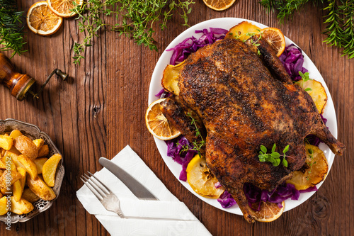 Baked whole duck, served with apples, red cabbage, oranges and roasted fritters.