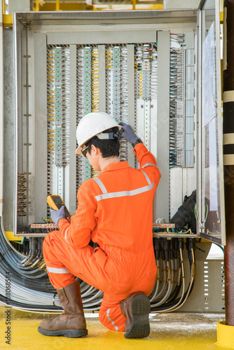 Cuadros en Lienzo  Electrical and instrument technician using digital multi meter measuring electric voltage on programmable logic controller ( PLC ) junction box at offshore oil and gas processing platform