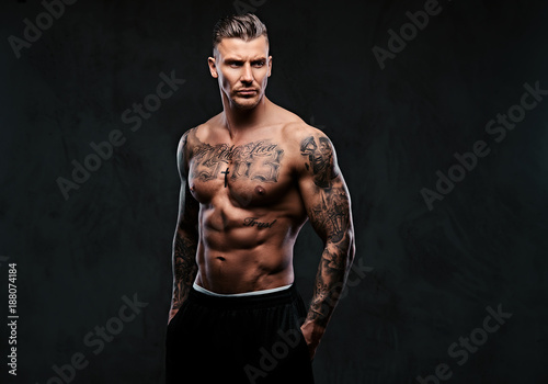 Fotografía  A muscular tattooed man on a dark background.