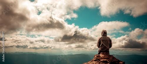 Cuadros en Lienzo Lonely man sitting on top of mountain cloudy sky