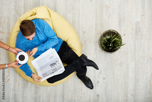 Bearded young man sitting on cozy beanbag chair and reading newspaper while his Poster