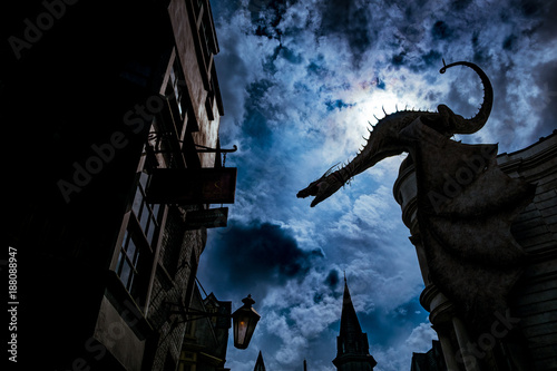 Fotografie, Obraz big fantasy dragon looming over houses in ancient magic town in obscure dim nigh