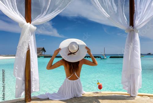 Frau mit weißem Hut genießt ihren Luxusurlaub auf den Malediven