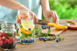 Blurred view of woman preparing infused water with fruits and berries in mason jar