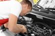Auto mechanic repairing car outdoors