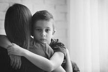 Sad Little Boy Hugging His Mother Indoors, Black And White Effect