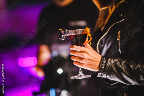 Photo  Girl in leather jacket holding coctail with grape on the glass