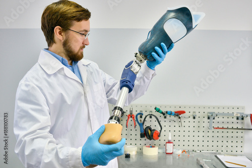 Portrait of young  prosthetics technician holding prosthetic leg  checking it fo Fototapeta