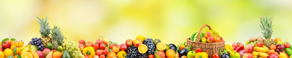 FototapetaFresh healthy fruits and vegetables in basket on natural blurry multicolored background.