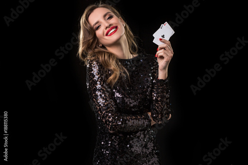 Fototapeta Young woman holding playing cards against a black background obraz na płótnie