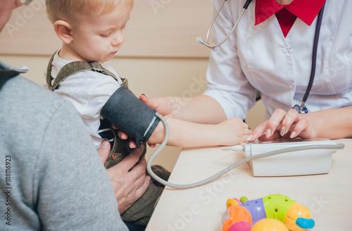 Plakat Lekarz mierzy ciśnienie krwi dziecka.