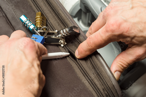 Obraz na plátně Open a locked suitcase zipper with a ballpoint pen
