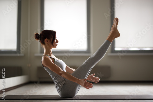 Photo  Young sporty woman doing yoga stretching exercise sitting in gym near bright win