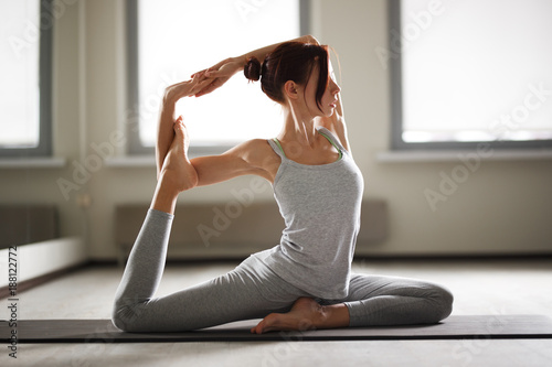 Poster School de yoga Young sporty woman doing yoga stretching exercise sitting in gym near bright windows