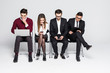 Young people are sitting in a row in business centre while waiting for the interview isolated on white