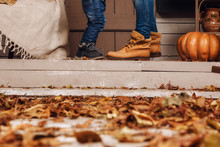 Legs Of Little Baby Boy And Mother Dressed In Jeans, Yellow And Blue Boots Staying On Porch Steps House In Autumn Time. Woman And Son On Courtyard, Lit By Flashlights, With Dry Fall Leaves, Pumpkins.