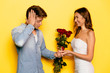 Happy attractive woman holding roses and box with engagement ring, making marriage proposal to her shocked and surprised boyfriend.