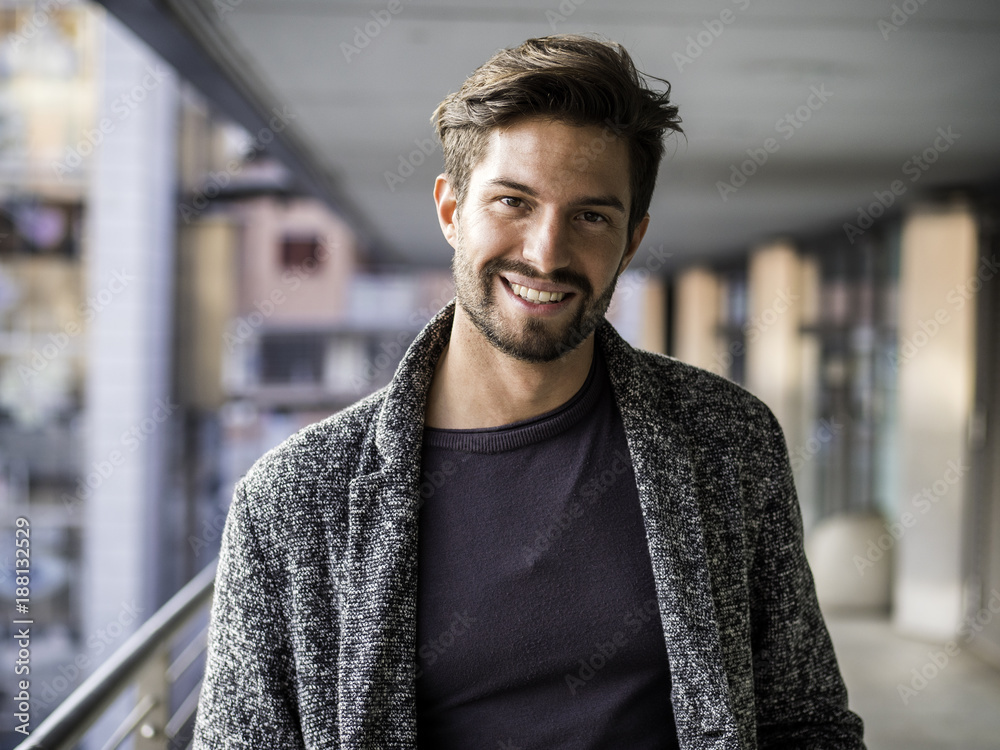 Fototapeta One handsome young man in urban setting in European city, standing and smiling to camera happy