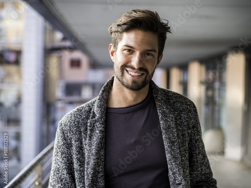 Obraz One handsome young man in urban setting in European city, standing and smiling to camera happy - fototapety do salonu