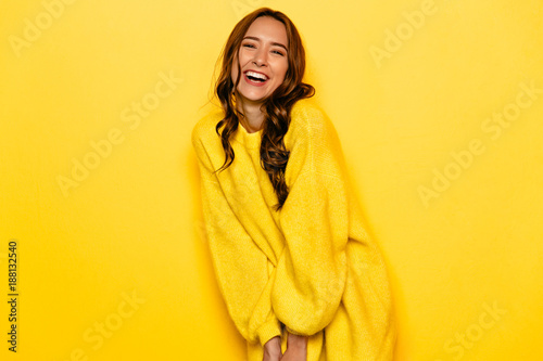 Funny young woman with curly hair in yellow sweater, widely smiling,. Isolated on yellow background.