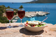 Two glasses of red wine and bowl of greek salad with greek flag on by the sea view, summer greek holidays concept.