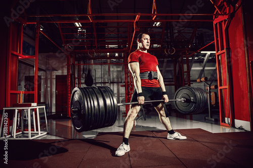 Fotografia  Muscular fitness man doing deadlift a barbell in modern fitness center