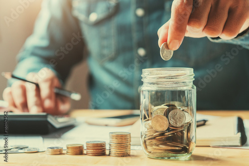 Photo  businessman holding coins putting in glass