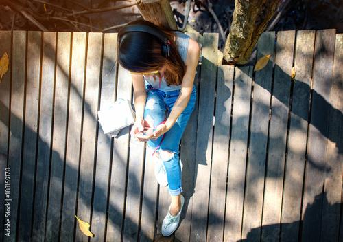woman enjoy listening musics and reading on wooden bridge under