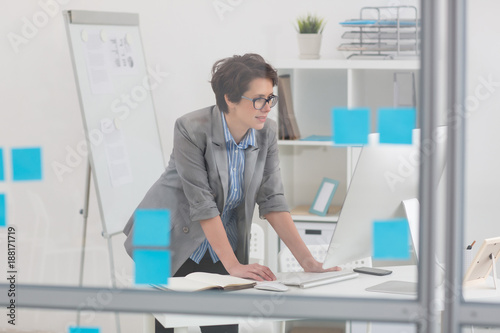 Vászonkép Woman in formalwear leaning over her desk and looking at display of computer mon