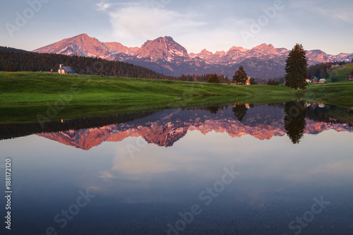 Foto auf Gartenposter Reflexion mountain village are reflected in the lake in the evening