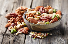 Mixed And Cut Nuts On A Wooden Background