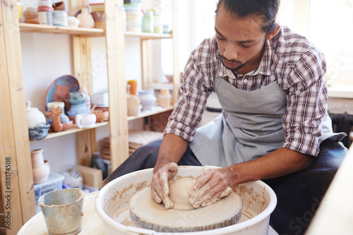 Creative Craftsman Making Pottery On Special Equipment In Workshop