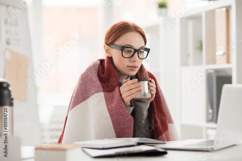 Photo Young woman in plaid and eyeglasses drinking hot tea from mug during work in off