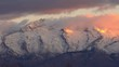 View of snow covered mountain peak and clouds as the sun lights it up at dawn.