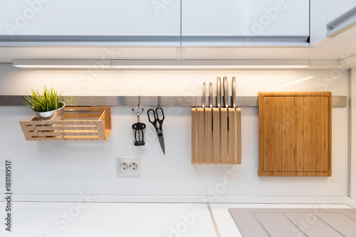 Fotografía  kitchenware hanging on the rail in the white glossy kitchen