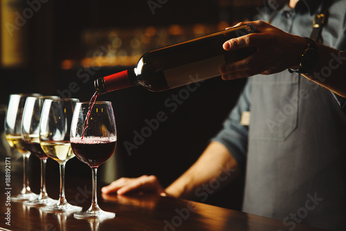 Bartender pours red wine in glasses on wooden bar counter