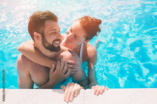 Fotografía Cheerful youthful guy and lady resting while swimming pool outdoor