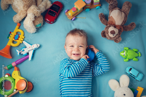 Obraz Happy one year old boy lying with many plush toys - fototapety do salonu