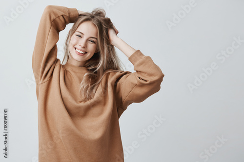 Beautiful pretty charming young blonde woman in loose sweater smiling happily, having fun indoors, playing with long straight hair Fototapet