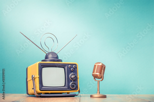 Retro old television receiver and golden microphone on table front gradient aquamarine wall background. Broadcasting concept. Vintage style filtered photo