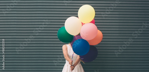 Photo  Happy young woman with colorful balloons on a street near the gray - outdoors su