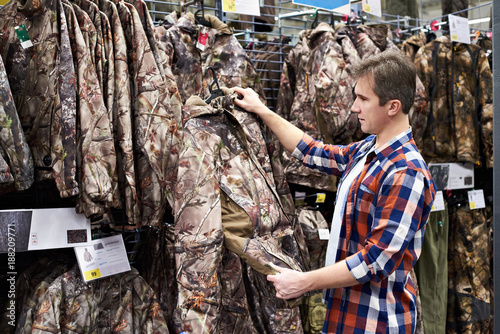 Foto op Canvas Jacht Man chooses clothes for hunting in sports shop