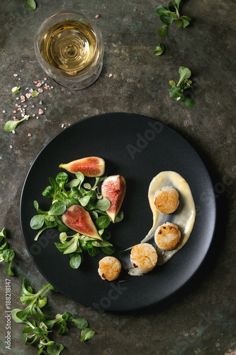 Fried scallops with lemon, figs, sauce and green salad served on black plate with glass of white wine over old dark metal background. Top view, space. Plating, fine dining