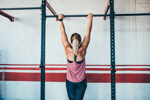 Strong female athlete doing pull up in gym