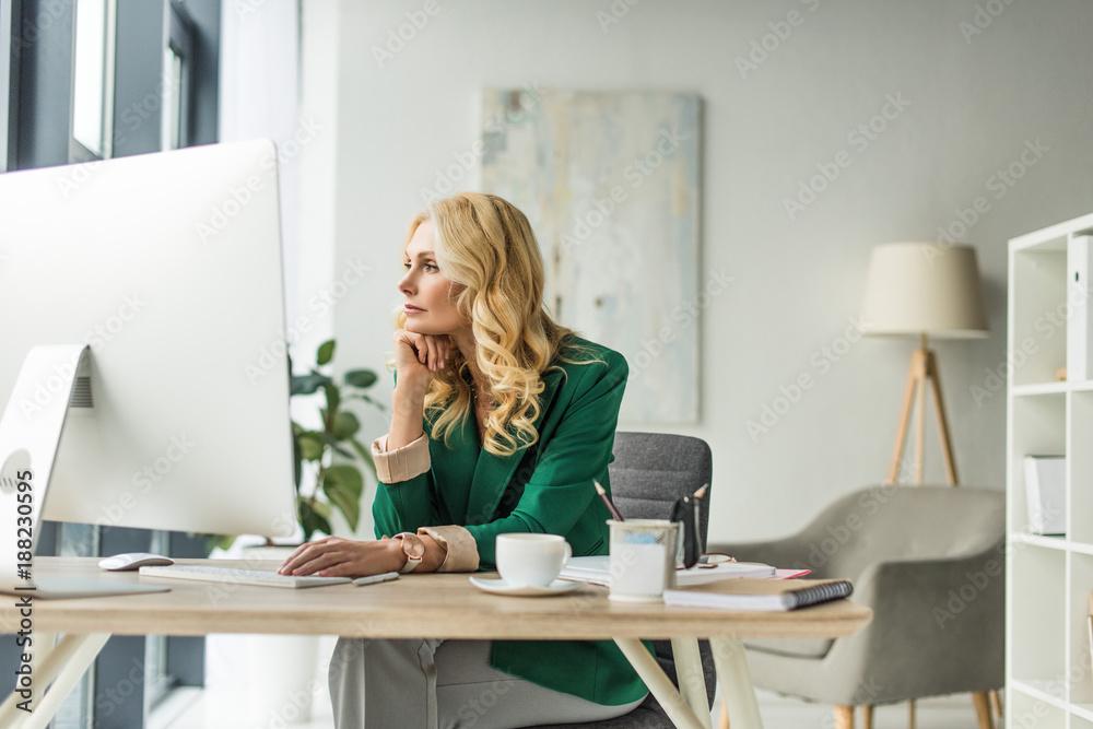 Fototapeta pensive businesswoman looking away while using desktop computer at workplace