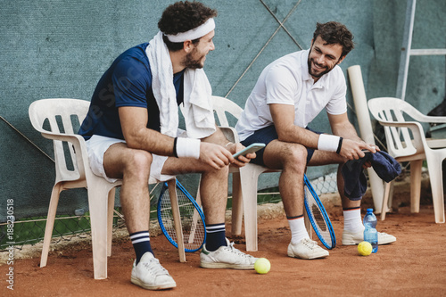 Two young men having a break after a tennis match on a clay court