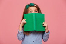 Cute Girl 5-6 Years Wearing Hair Hoop Having Fun While Reading Interesting Book With Eyes Wide Open Isolated Over Pink Background